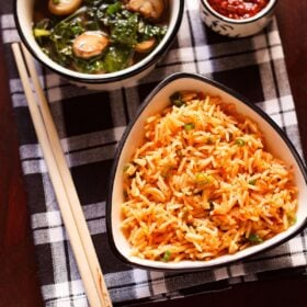 top shot of schezwan fried rice in a black rimmed triangular bowl with bamboo chopsticks at the side on a checkered black and white napkin