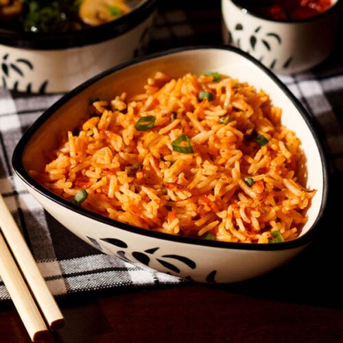 schezwan fried rice in a black and white triangular bowl with bamboo chopsticks at the side