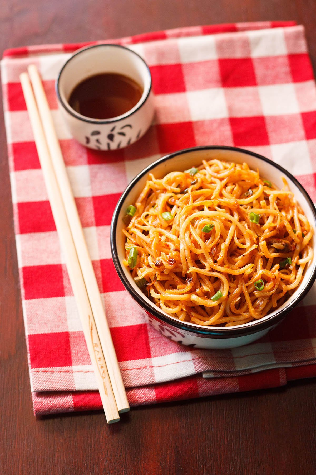 schezwan noodles in a black rimmed cream bowl with bamboo chopsticks at the side and a small bowl of schezwan sauce placed on a checkered red and white napkin
