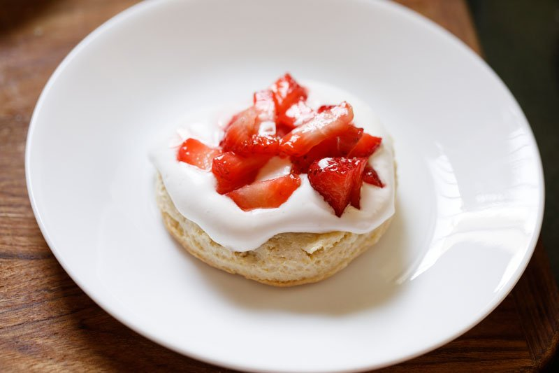 shortcake halve topped with whipped cream and macerated strawberry stuffing and juices