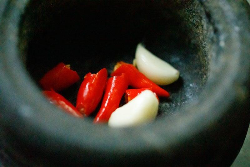 garlic cloves and bird's eye chilis in a mortar