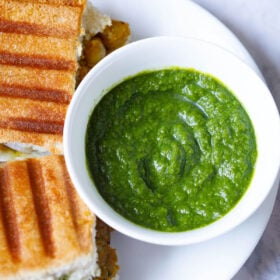 top shot of coriander chutney in white bowl placed next to grilled sandwiches on a white plate