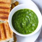top shot of cilantro chutney in white bowl placed next to grilled sandwiches on a white plate