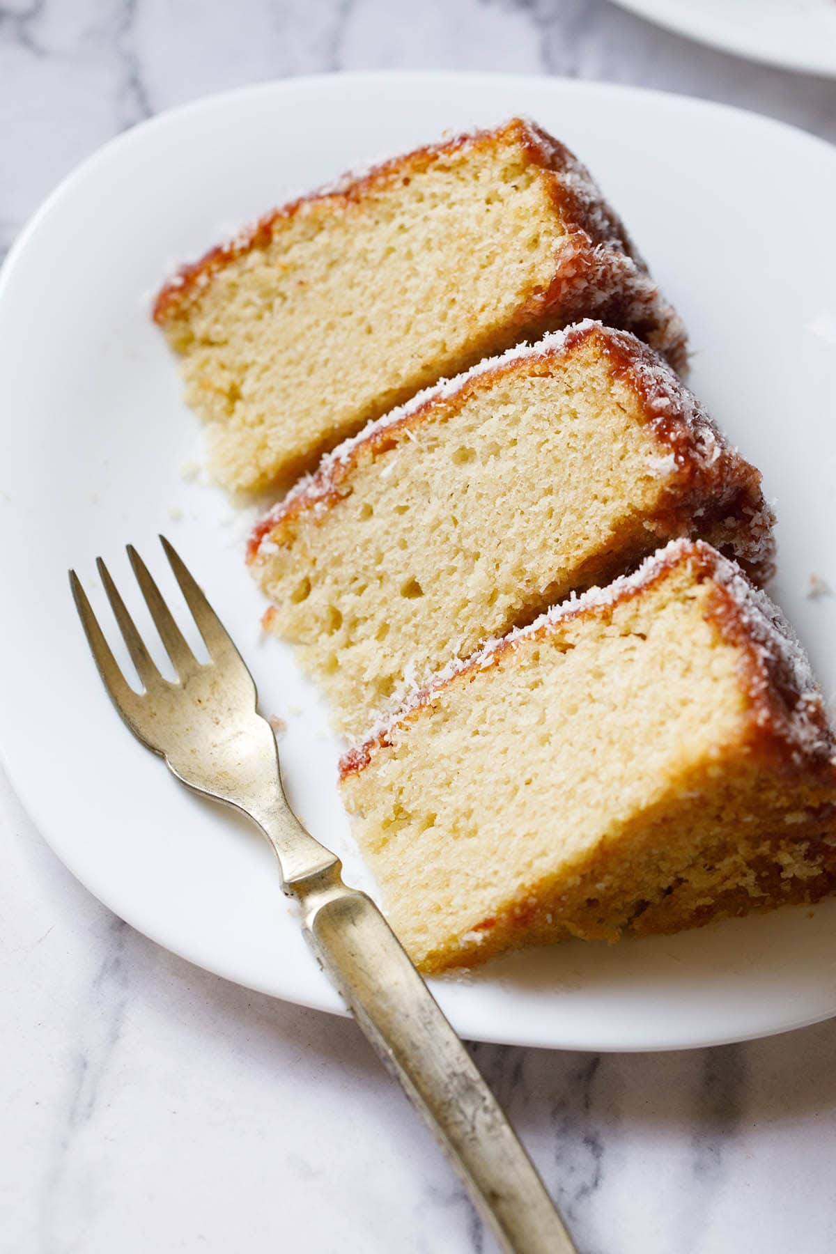 close up shot of thick slices of eggless vanilla cake on a square shaped white plate woth a brass fork on the plate