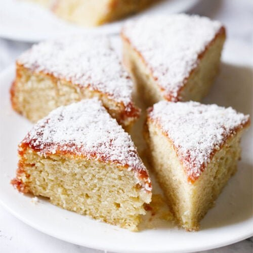 vanilla cake triangular wedges topped with jam icing and desiccated coconut on a white plate