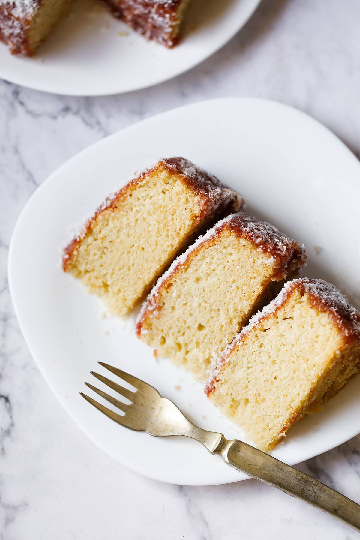 top shot of thick slices of eggless vanilla cake on a square shaped white plate woth a brass fork on the plate