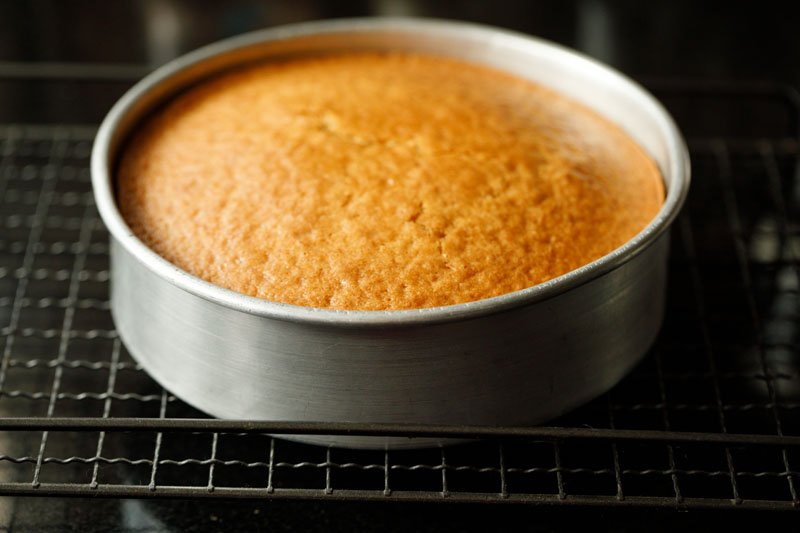 baked vanilla cake in the pan on a rack