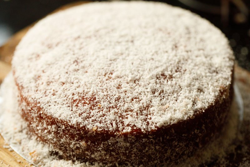 eggless vanilla cake with jam icing topped with desiccated coconut
