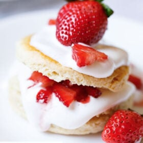 close up shot of strawberry shortcake with the cream and strawberry filling seen and topped with some and a large strawberry on top on a white plate