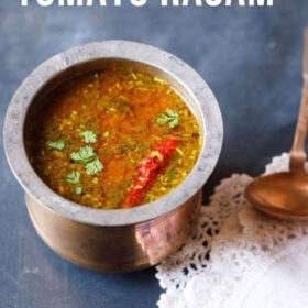tomato rasam in a traditional South Indian container with a spoon placed on top of a white kitchen napkin on the left side on a blue board