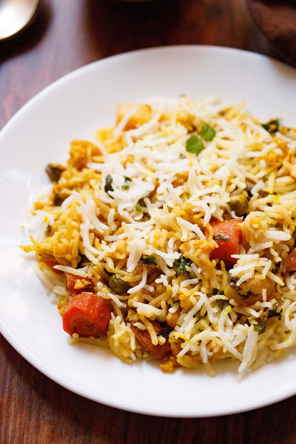 close up shot of biryani on white plate on wooden table
