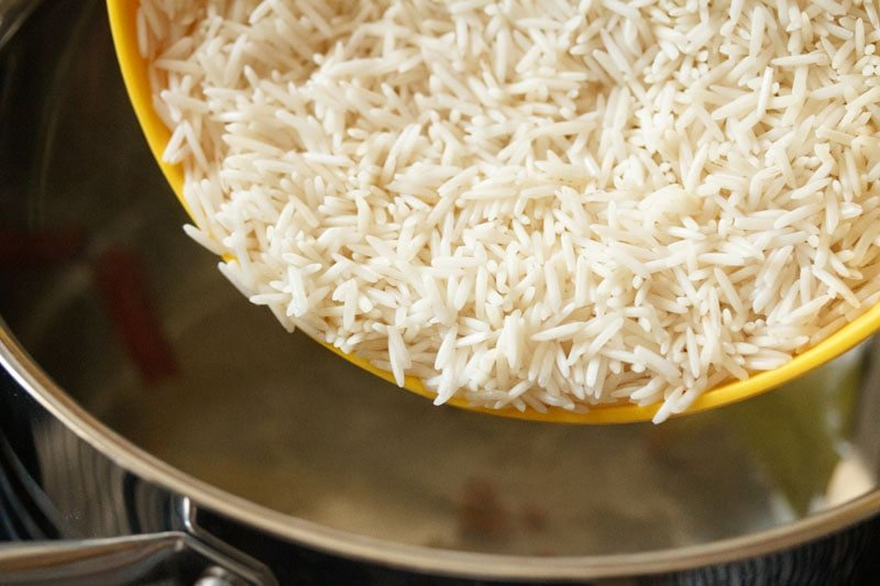 Soaked white rice being poured from yellow bowl into pot