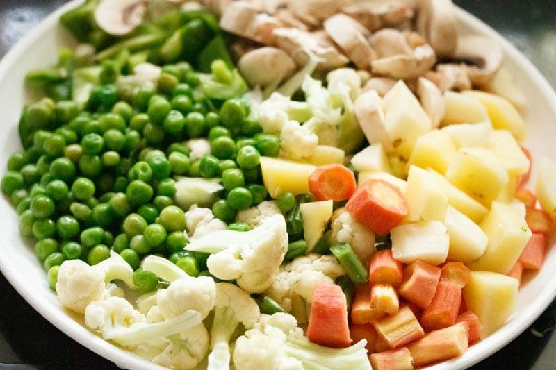 Top shot of chopped vegetables on white plate for veg biryani recipe