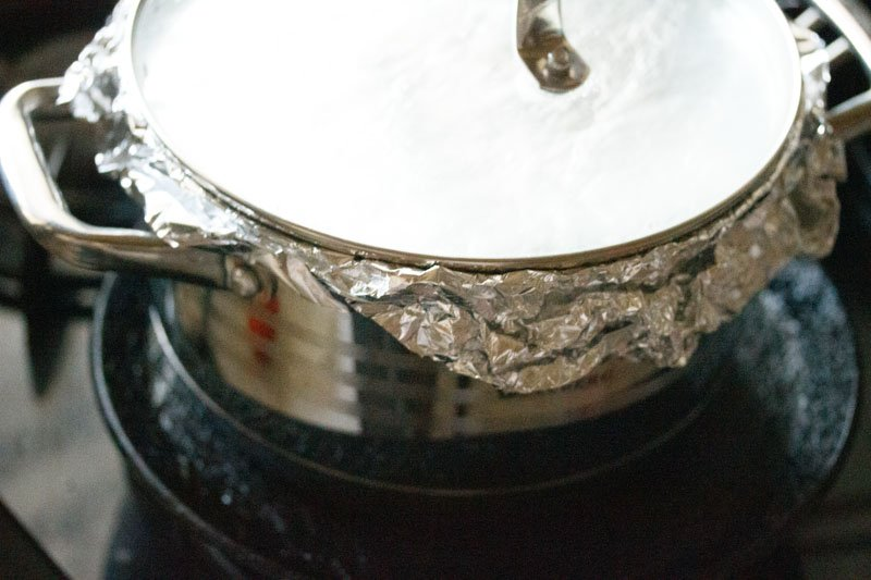 Top shot of closed pot with aluminum foil placed on a black tawa (skillet)