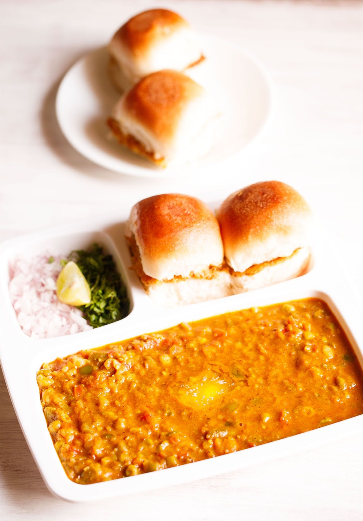 bombay pav bhaji served in a rectangular serving tray with buttered pav and chopped onions, cilantro and lemon wedges on a white table