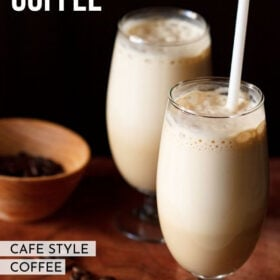 side shot of cold coffee in two glass with a white straw in one glass with coffee beans in a dark orange bowl and some coffee beans on a wooden board with a text layover