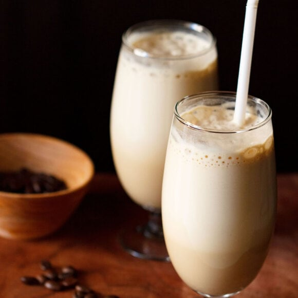 side shot of cold coffee in two glass with a white straw in one glass with coffee beans in a dark orange bowl and some coffee beans on a wooden board