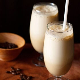 side shot of cold coffee in two glasses with a white straw in one glass with coffee beans in a dark orange bowl and some coffee beans on a wooden board