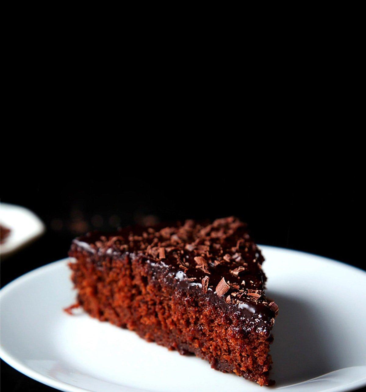 A triangular wedge of eggless chocolate cake on a white plate