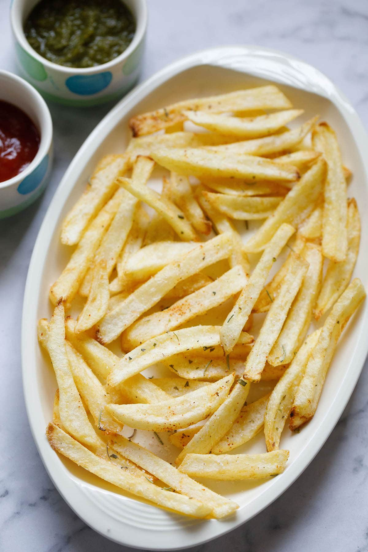 white serving tray filled with homemade french fries next to small dipping bowls of ketchup and green chutney