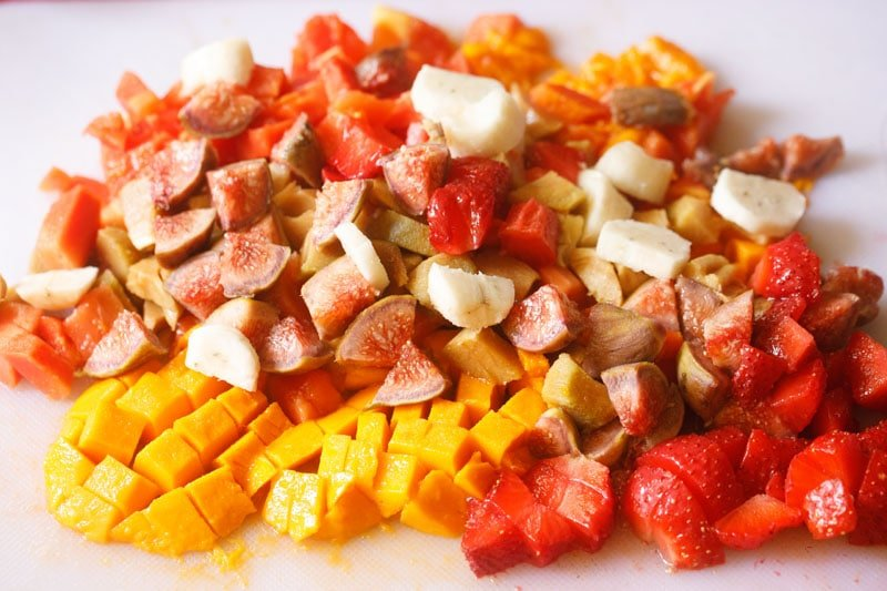 mango, papaya, chickoo, strawberries, figs and bananas all chopped into bite sized pieces on a white table
