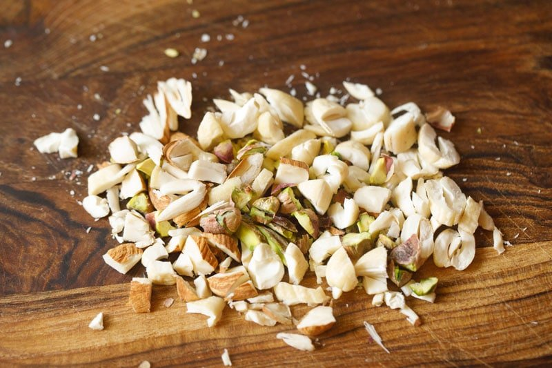chopped trio of nuts on a wooden cutting board