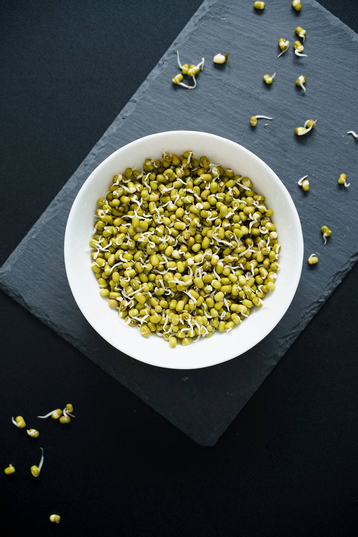green gram sprouts in a white bowl on a gray slate board on a black board