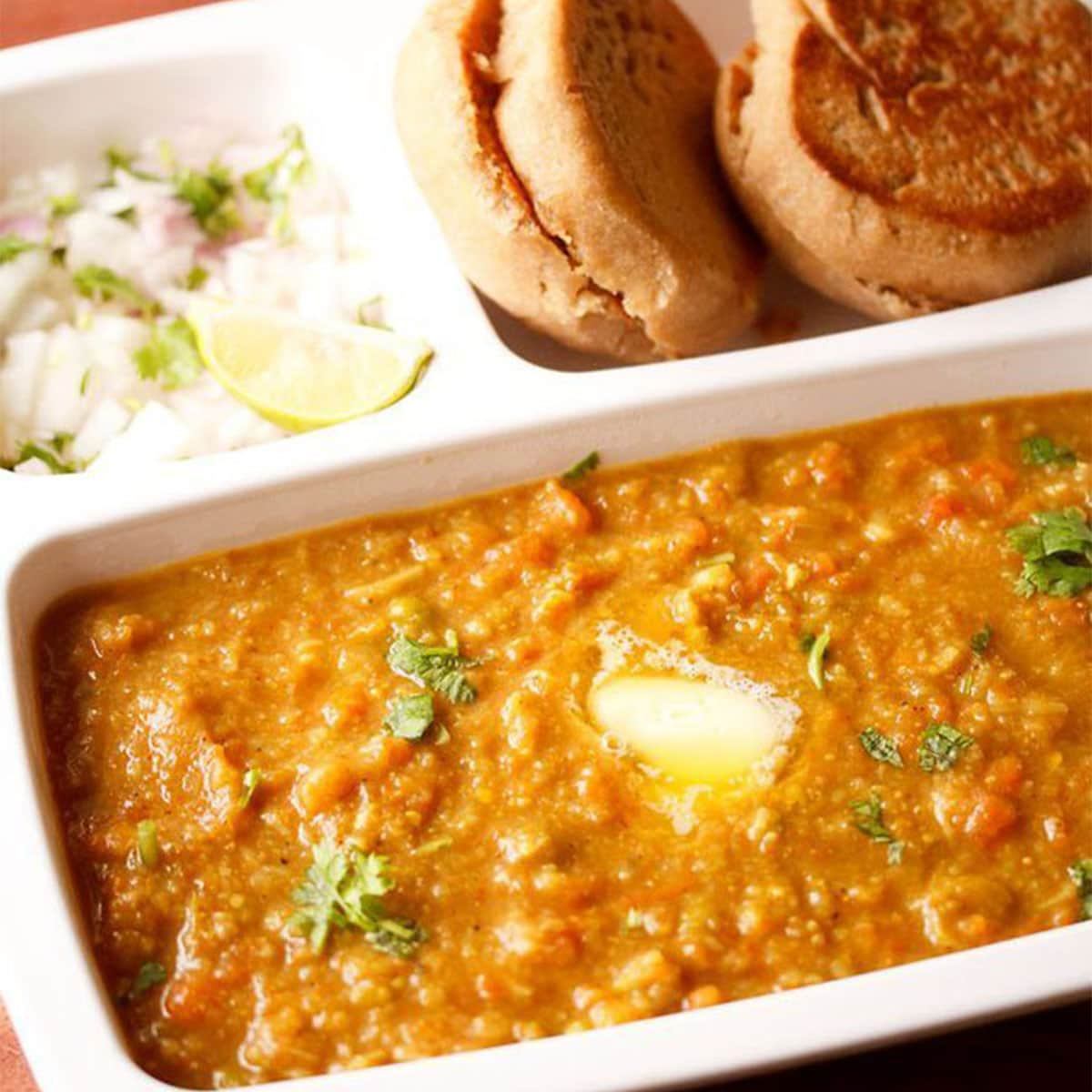 instant pot pav bhaji garnished with cilantro and served in a white tray with toasted rolls and chopped onions and lemons
