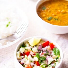 kachumber salad in a small white bowl on a table next to plate of rice and a bowl of lentils