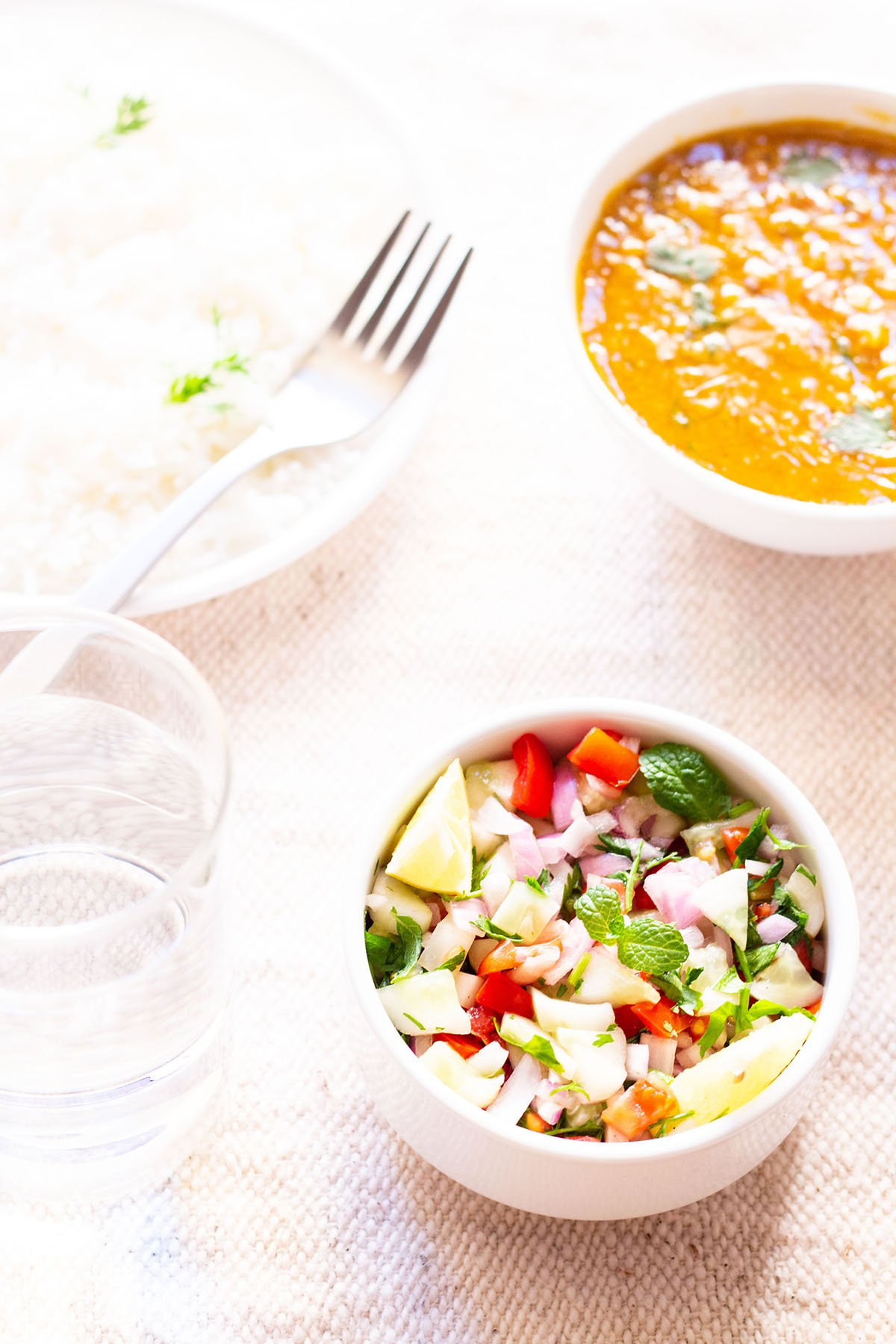 kachumber salad in a small white bowl on a table next to bowls of rice and curry