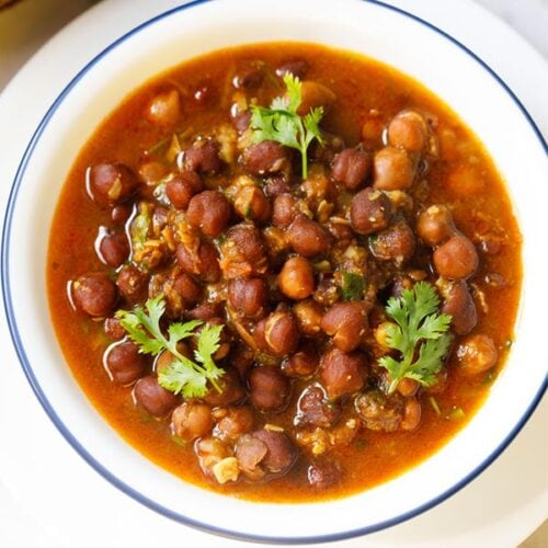 kala chana gravy with three coriander sprigs on top in a blue rimmed white bowl