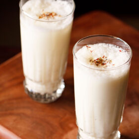 sweet lassi topped with crushed cardamom powder and saffron in two tall glasses on a wooden board
