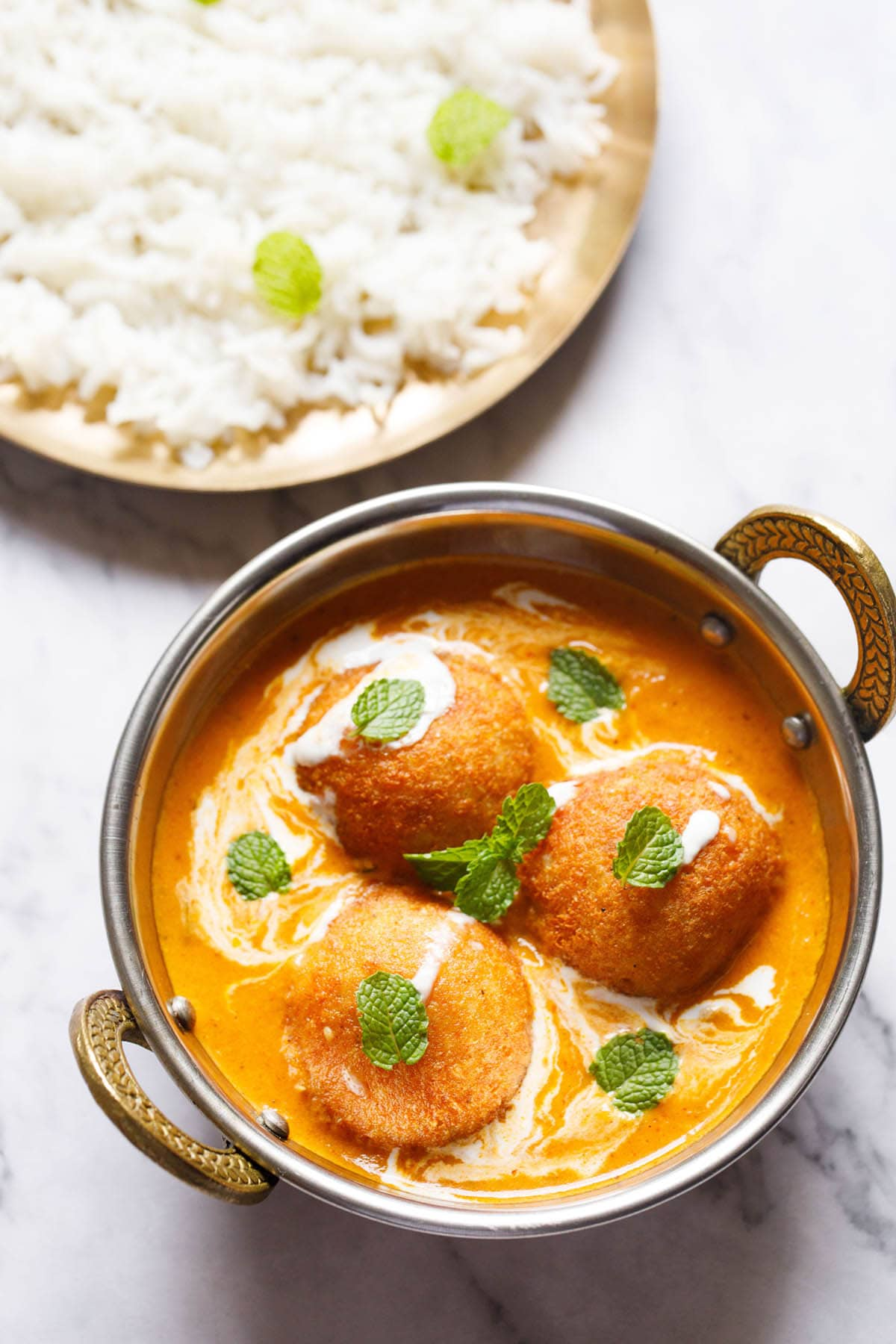top shot of 3 malai kofta with mint leaves on top in a silver serving dish with handles on a white marble