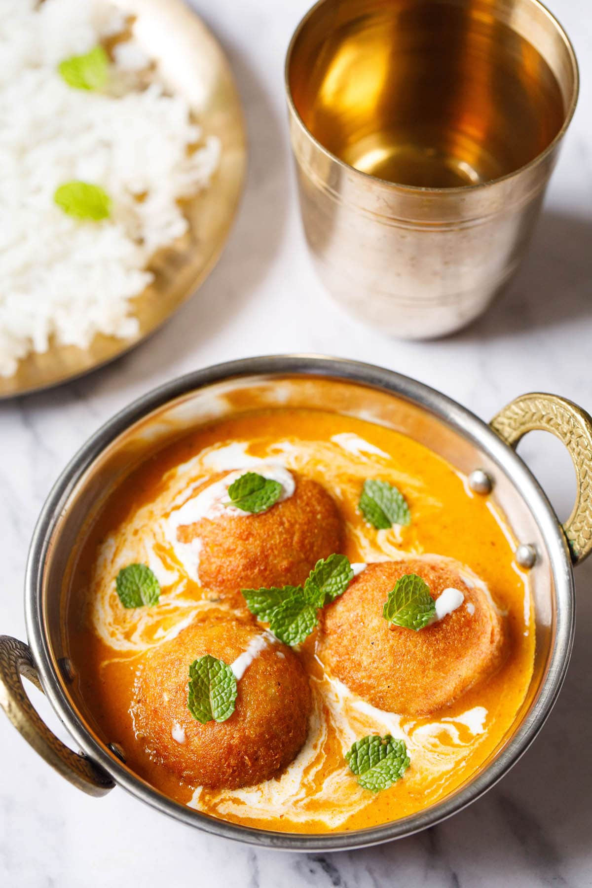 3 malai kofta garnished with mint leaves in a silver serving dish with handles on a white marble