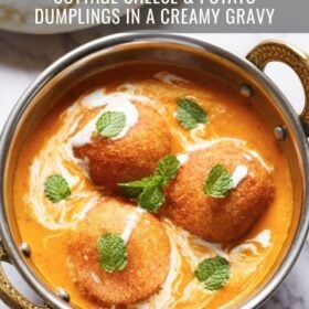 top shot of 3 malai kofta garnished with mint leaves in a silver serving dish with handles on a white marble with text layovers
