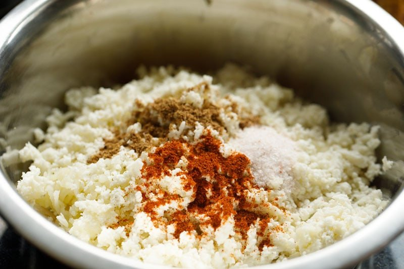 ground spices, grated paneer on the grated potatoes