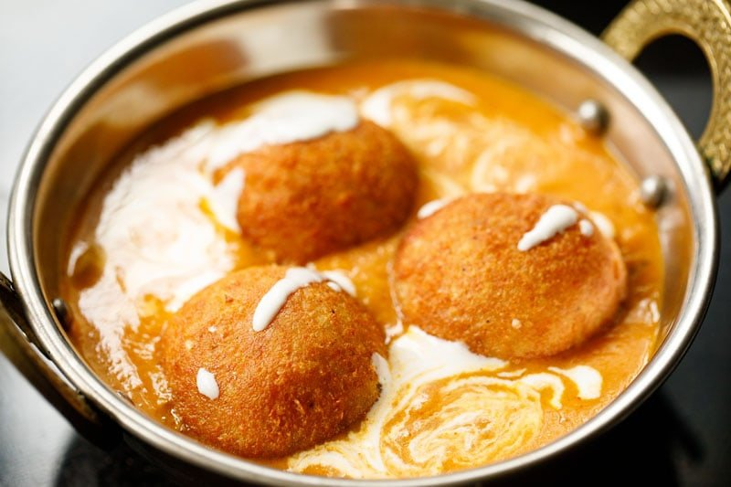 three malai kofta placed on the gravy with a drizzle of cream on top