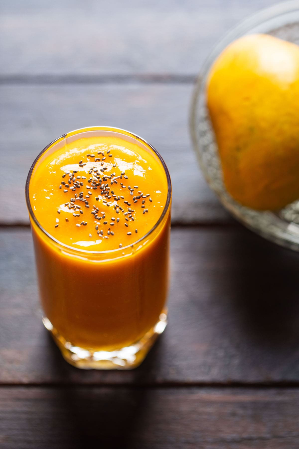 closeup shot mango juice in a glass topped with chia seeds on a wooden table with a side of mangoes on a glass bowl