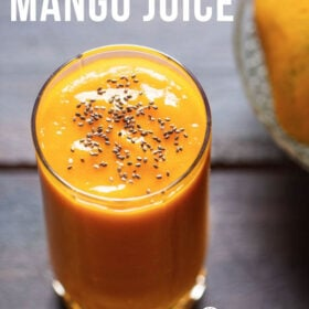 top shot shot of mango juice in a glass topped with chia seeds on a wooden table with a side of mangoes on a glass bowl with a text layover