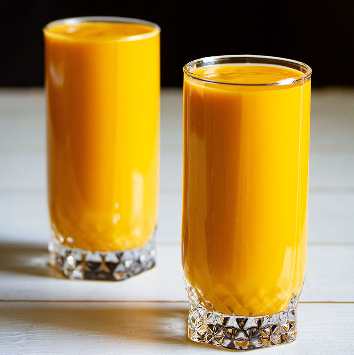 mango milkshake in two tall glasses on white table with a black background