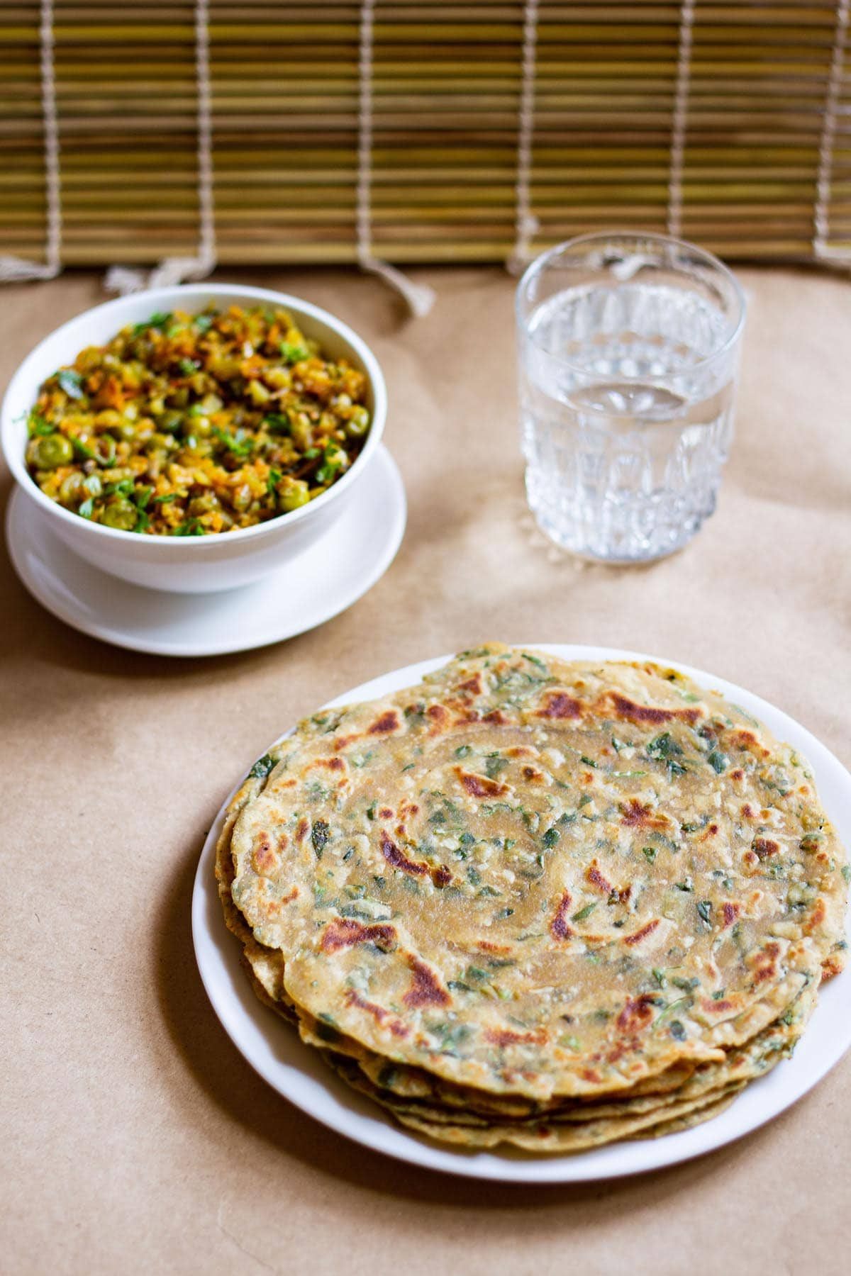 a stack of methi paratha in a white plate with a veggie dish in white bowl and glass of water