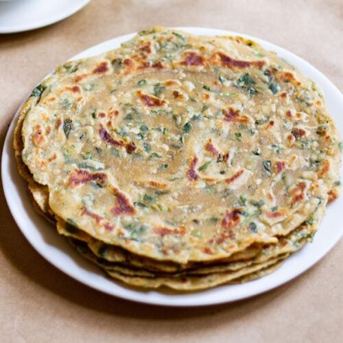 a stack of methi paratha in a white plate