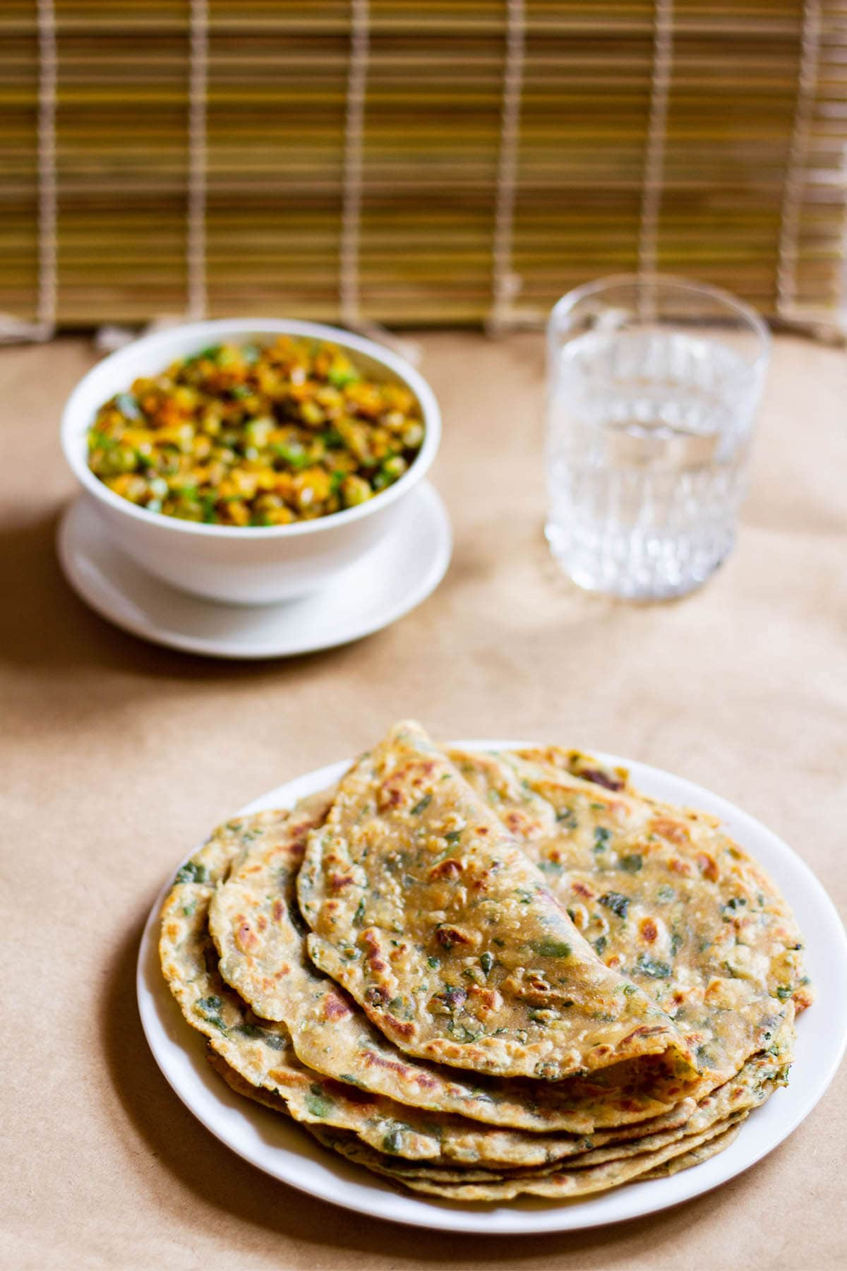 folded methi paratha on a stack of methi parathas in a white plate with a veggie dish in white bowl and glass of water