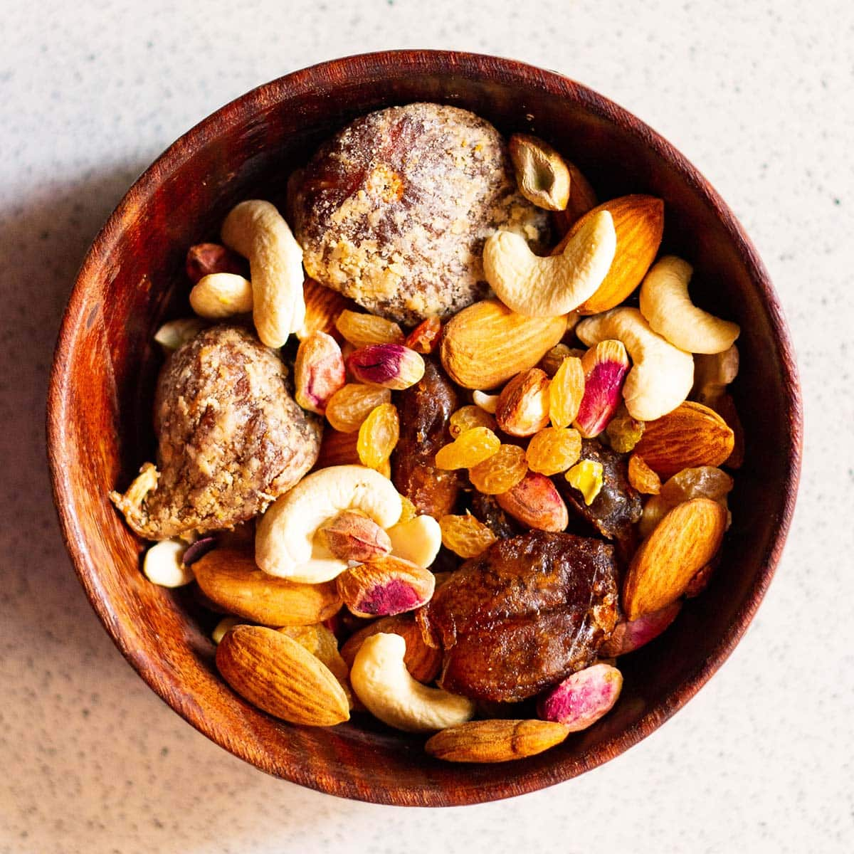 various nuts and dry fruits in a woodern bowl on a marble surface
