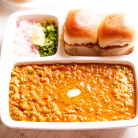 pav bhaji served in a rectangular serving tray with buttered pav and chopped onions, cilantro and lemon wedges on a white table