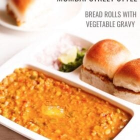 pav bhaji served in a rectangular serving tray with buttered pav and chopped onions, cilantro and lemon wedges on a white table with text layovers