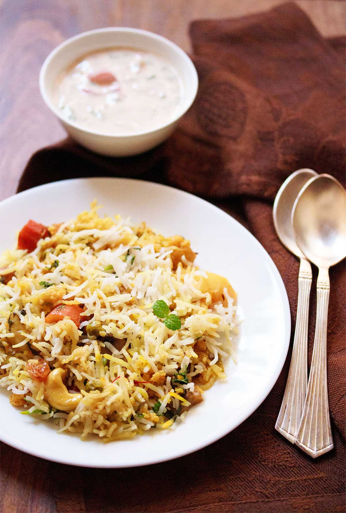 Top shot of veg biryani on white plate next to yogurt raita in small white bowl and two spoons on wooden table