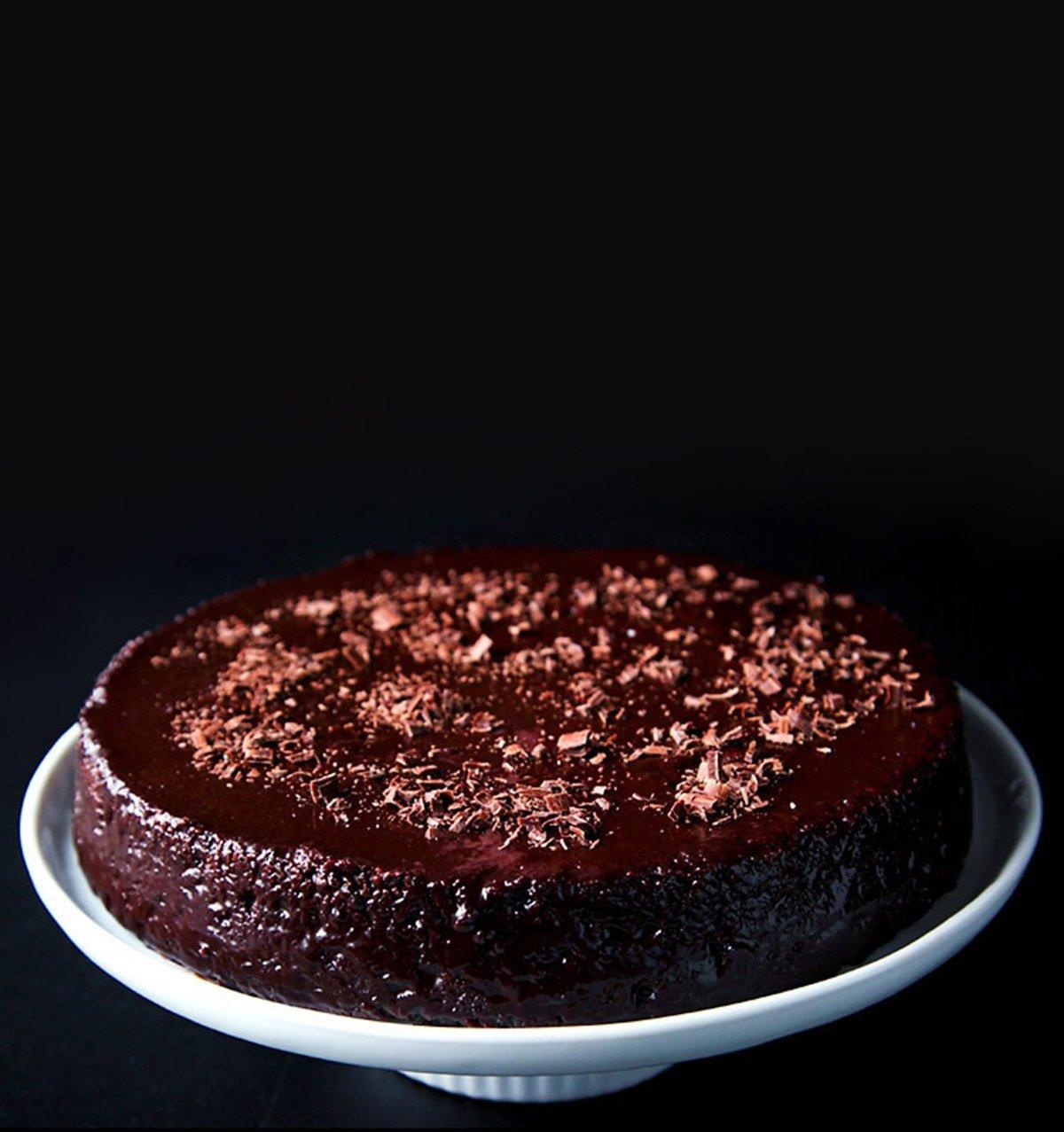 vegan eggless chocolate cake on a white cake stand on a black board