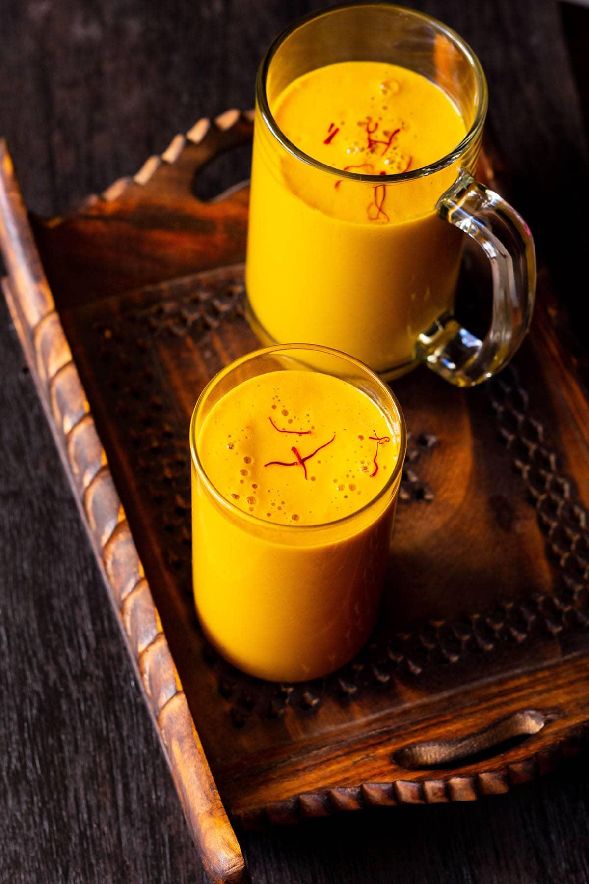 vegan mango milkshake in glass and a mug sprinkled with few saffron strands on a dark brown wooden tray