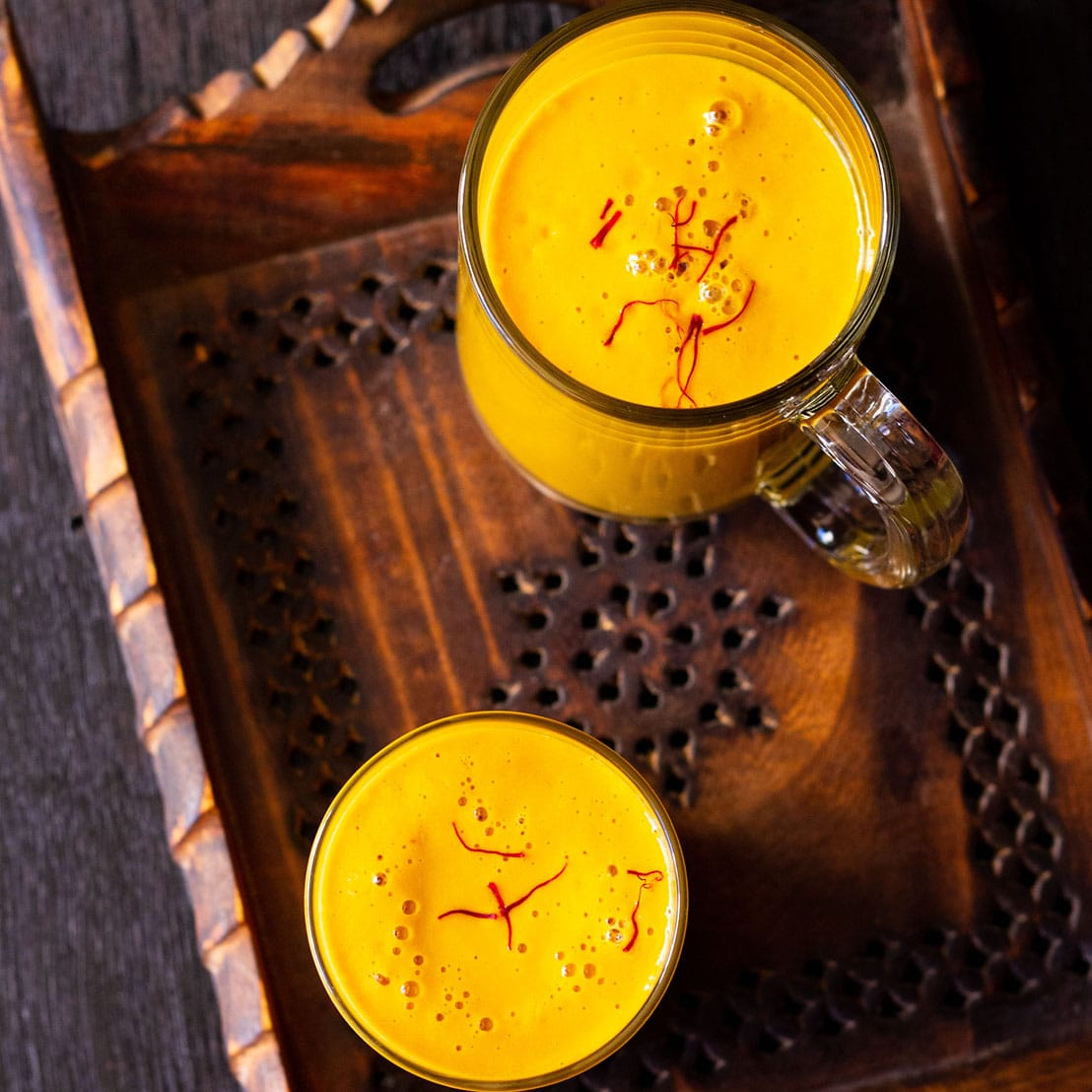 overhead shot of vegan mango shake in glass and a mug sprinkled with few saffron strands on a dark brown wooden tray